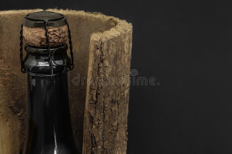 Szampańska czarna szklana butelka umieszczająca w drzewnej barkentynie na czarnym tle obraz royalty free