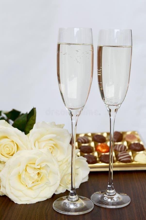 Szampańscy szkła, pudełko czekolada i wiązka Białe róże, fotografia royalty free