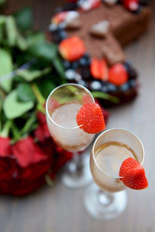 Szampańscy szkła z truskawkami i wiązką kwiaty obraz royalty free