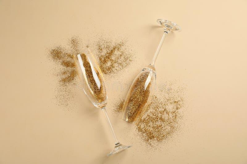 Szampańscy szkła z złocistą błyskotliwością na beżowym tle Komicznie świętowanie zdjęcia stock