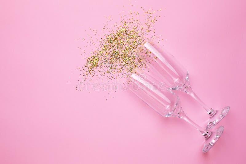 Szampańscy szkła z złotymi confetti na menchiach barwią papierowego tła minimalnego styl obraz stock