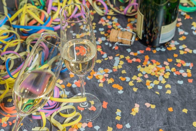 Szampański szkło i butelka z karnawałową dekoracją na łupku fotografia stock