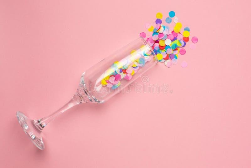 Szampański szkło z barwiącymi confetti na menchiach barwi papierowego tło Mieszkanie nieatutowy sk?ad dla urodziny, macierzysty d obraz stock
