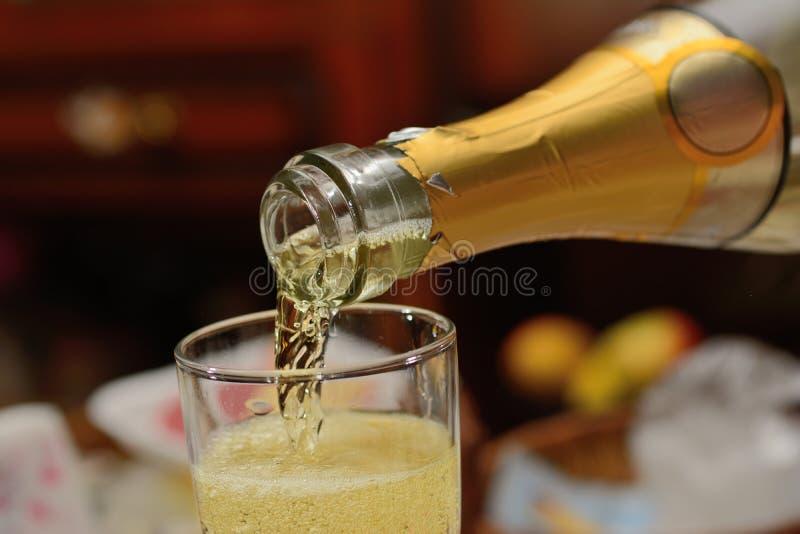 Szampanowi od butelki nalewają wewnątrz szklanego zakończenie w górę obrazy stock