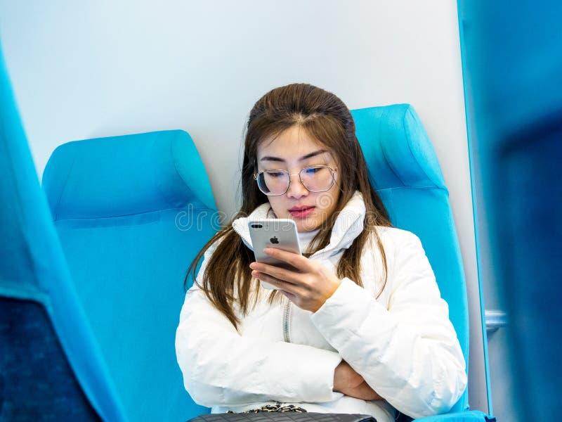 SZANGHAJ, CHINY 13 MARZEC 2019 - młoda Chińska kobieta przewodzi Pudong zawody międzynarodowi używa Jabłczanego iphone na Maglev  obraz royalty free