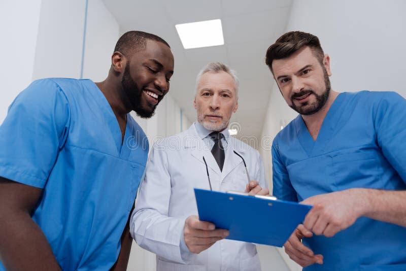 Szanujący pediatra cieszy się rozmowę z kolegami w klinice fotografia royalty free