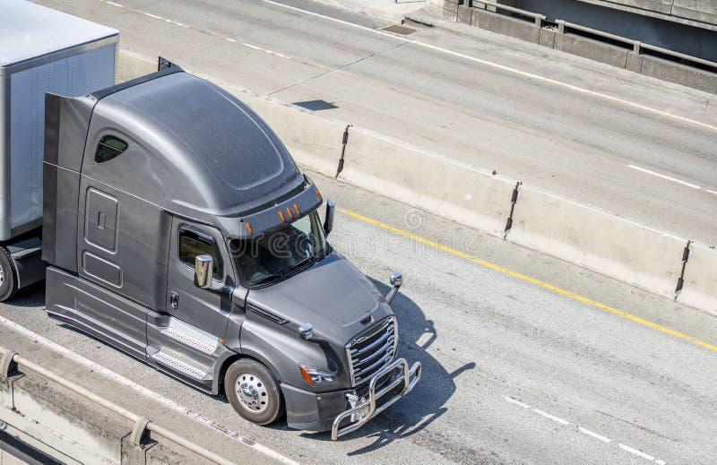 Szara duża takielunku dalekiego zasięgu semi ciężarówka odtransportowywa semi przyczepę z handlowym ładunku bieg na szerokiej mul fotografia royalty free