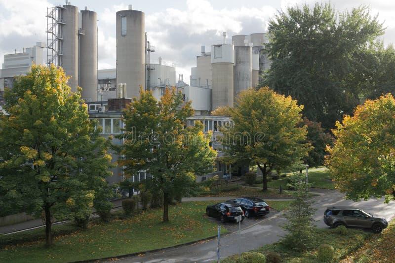 Szara fabryka z zielonymi drzewami i parking zdjęcia stock