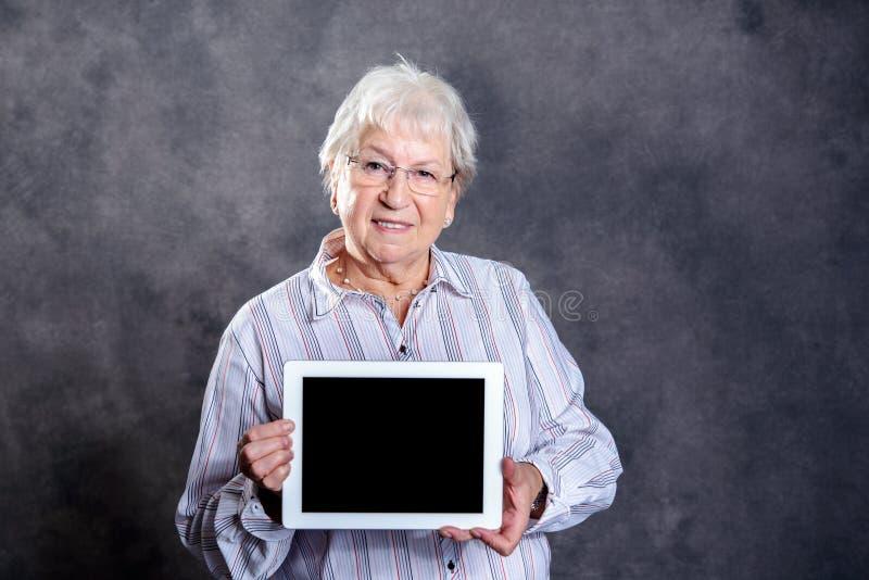 Szara kosmata starsza kobieta używa pastylka komputer osobistego obraz stock