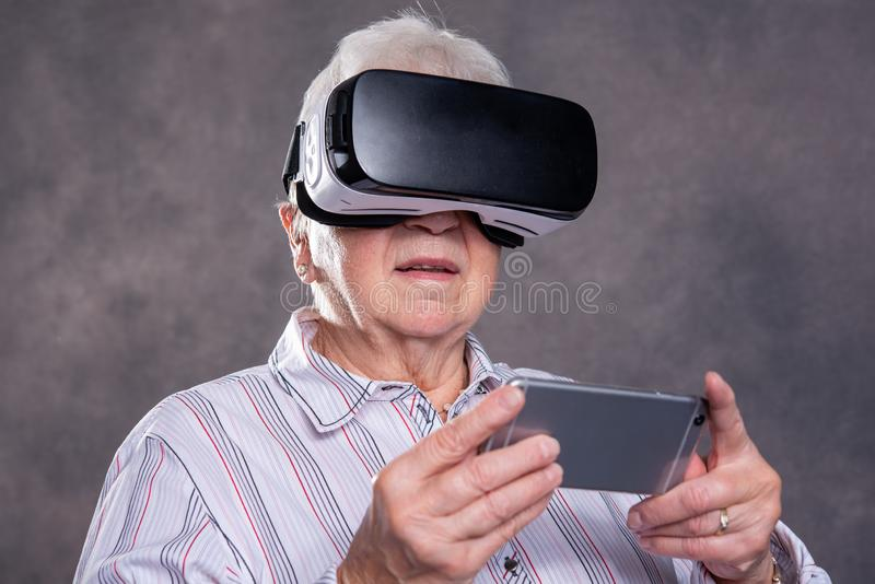 Szara kosmata starsza kobieta używa rzeczywistość wirtualna szkła zdjęcie royalty free