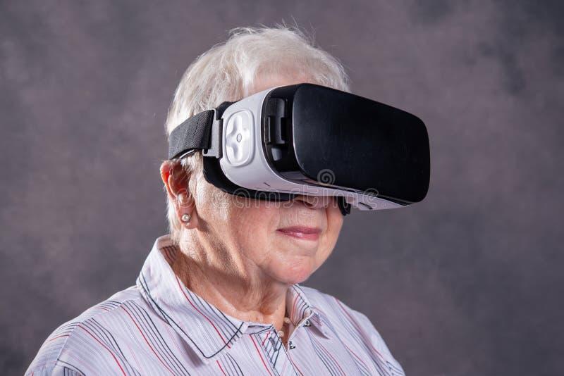 Szara kosmata starsza kobieta używa rzeczywistość wirtualna szkła obraz royalty free