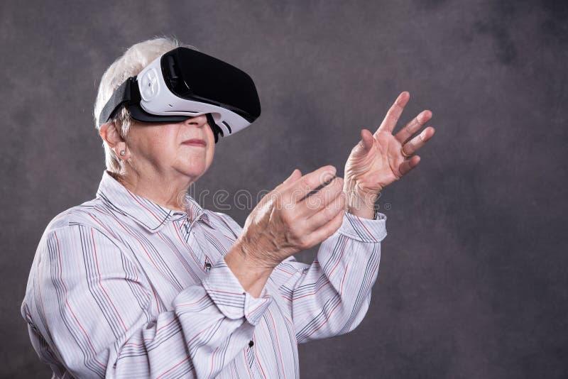 Szara kosmata starsza kobieta używa rzeczywistość wirtualna szkła zdjęcia royalty free