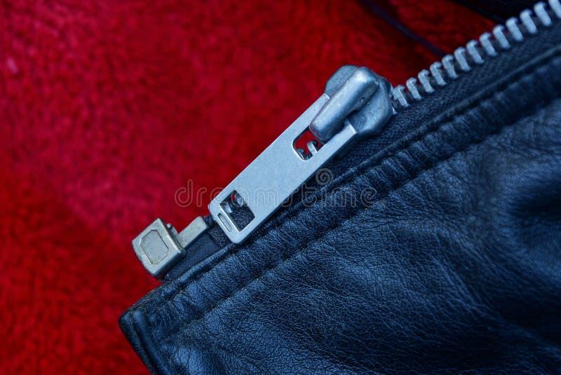 Szara metal klamra na skórze odziewa na czerwonym płótnie fotografia royalty free
