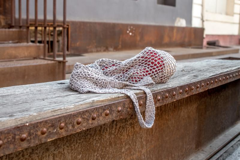 Szara smyczkowa torba z czerwonymi dziewiarskimi gejtawami na starej drewnianej ławce zdjęcie stock