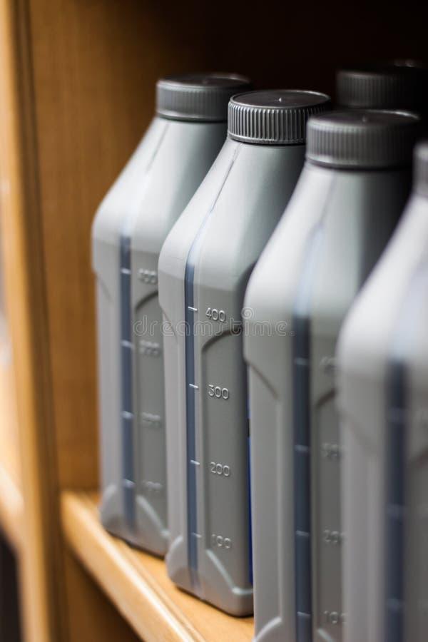 Szare plastikowe puszki motorowi oleje fotografia stock
