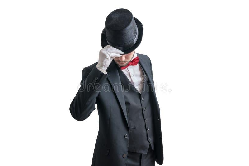 Szarmancki magik lub iluzjonista w kostiumu bierzemy daleko jego kapelusz pojedynczy białe tło zdjęcia stock