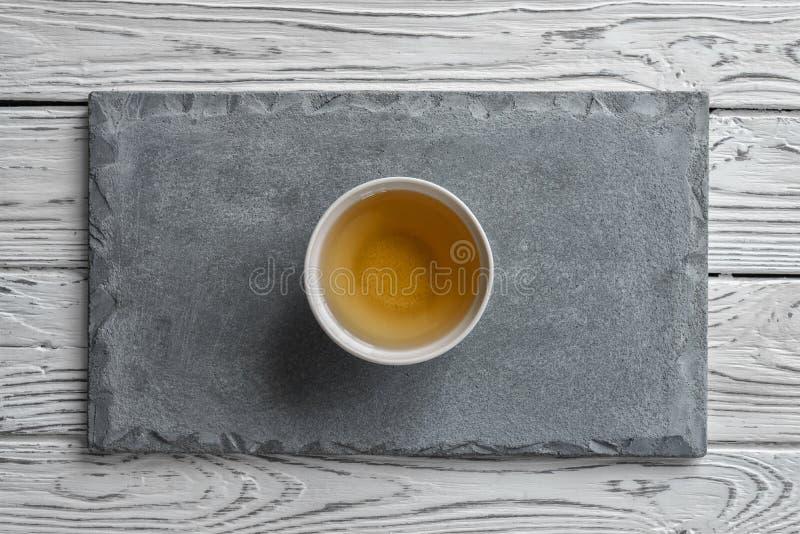 Szarość betonu talerz na lekkim drewnianym tle i filiżanka herbata obraz stock