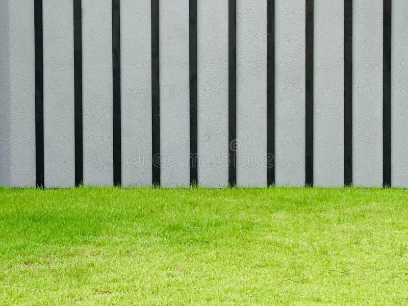 Szarość i czerni ściana z zieloną trawą obrazy royalty free