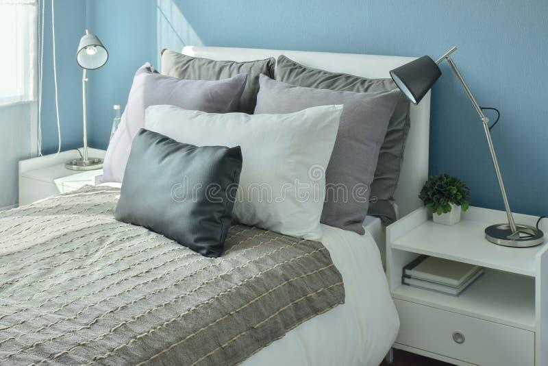 Szarość, poduszki na łóżku z błękit ścianą, zmroku - szare i beżowe obraz royalty free