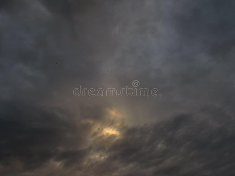 Szary chmurny, burzowy, ciemny niebo z ciemnymi dramatycznymi chmurami z jaskrawym żółtym pogodnym punktem w centrum z czarnymi p zdjęcie stock