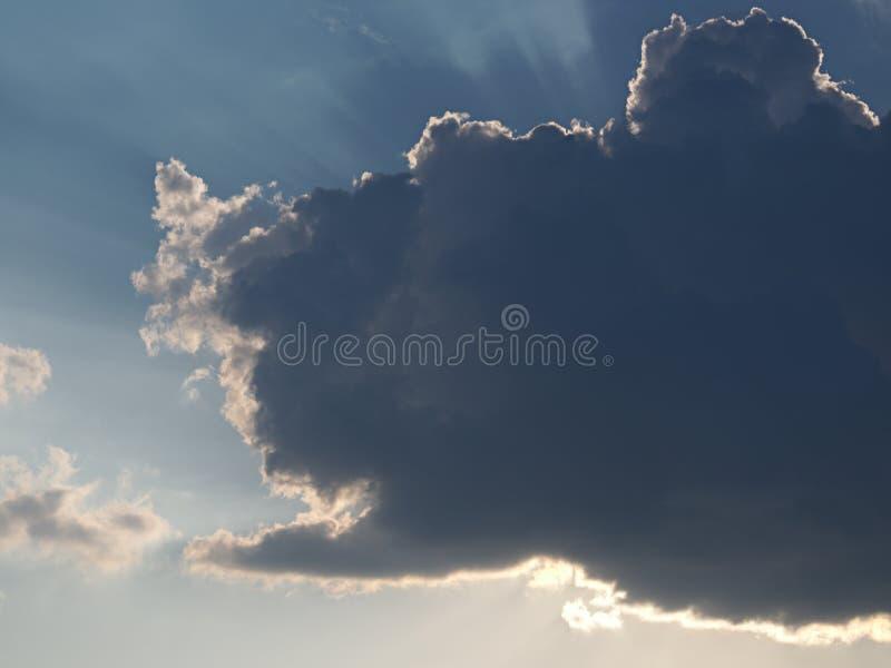 Szary cumulus na niebieskim niebie zakrywa słońce z słońce promieniami nadchodzącymi od chmury za out zdjęcia stock