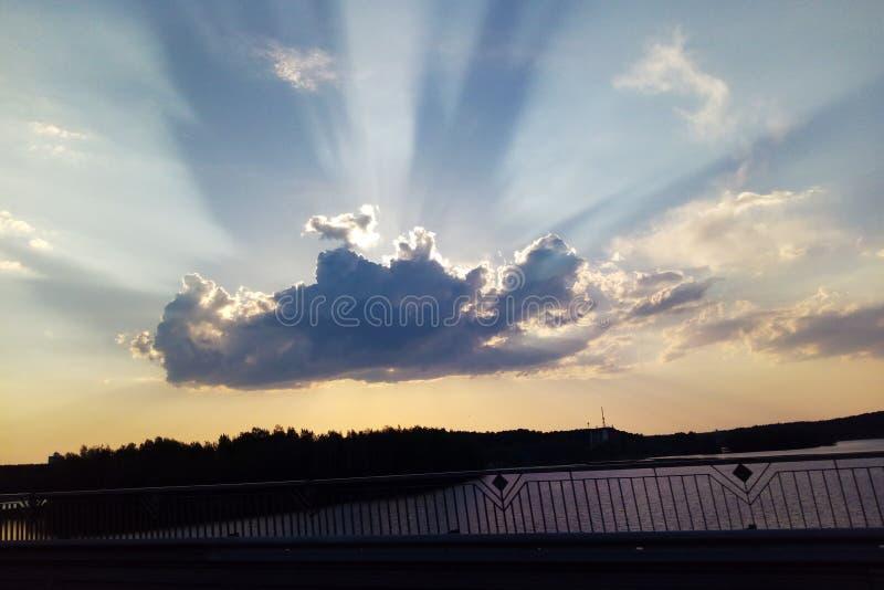 Szary cumulus na niebieskim niebie zakrywa słońce z słońce promieniami nadchodzącymi od chmury za out Wielka szarobiała chmura z  zdjęcie royalty free