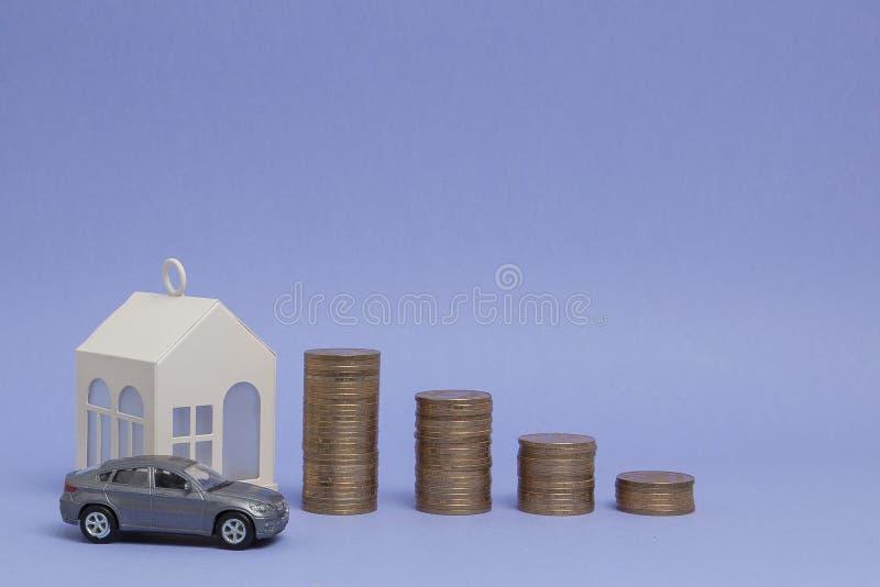 Szary maszynowy model i dom z monetami w postaci histograma na purpurowym tle Poj?cie po?yczanie, savings, sprzeda?, arenda zdjęcie royalty free