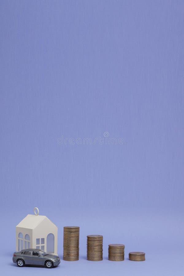 Szary maszynowy model i dom z monetami w postaci histograma na purpurowym tle Poj?cie po?yczanie, savings, sprzeda?, arenda zdjęcia stock