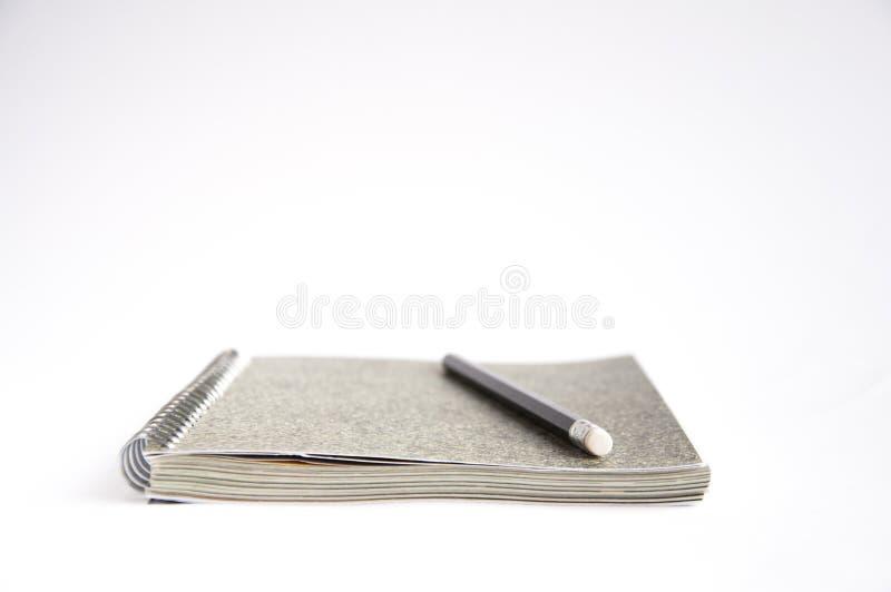 Szary notatnik kłama na stole Na ochraniaczu lub pobliski ja jest czarnym ołówkiem zdjęcia stock