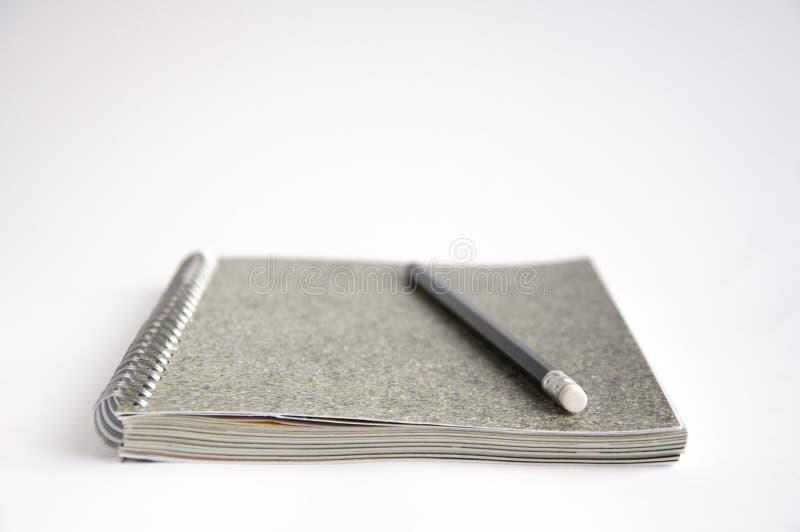 Szary notatnik kłama na stole Na ochraniaczu lub pobliski ja jest czarnym ołówkiem zdjęcie stock