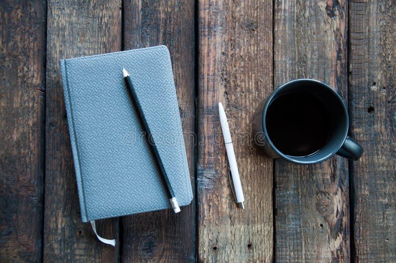 Szary notepad na stole Obok filiżanka kawy i pióra Na drewnianym zdjęcia royalty free