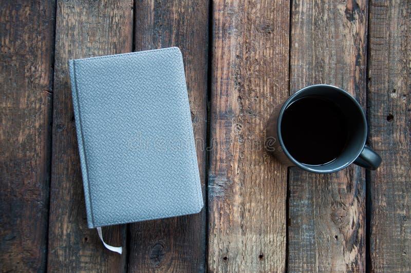 Szary notepad na stole Obok filiżanka kawy i pióra Na drewnianym obraz stock