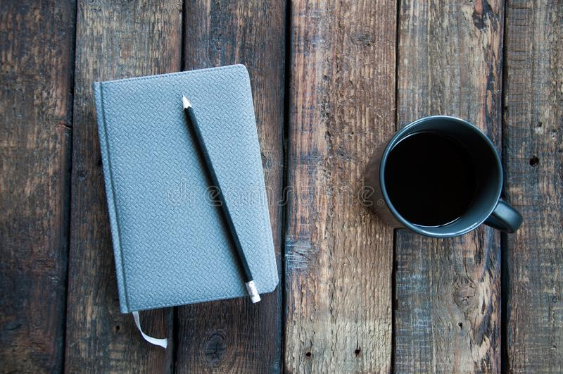 Szary notepad na stole Obok filiżanka kawy i pióra Na drewnianym fotografia stock