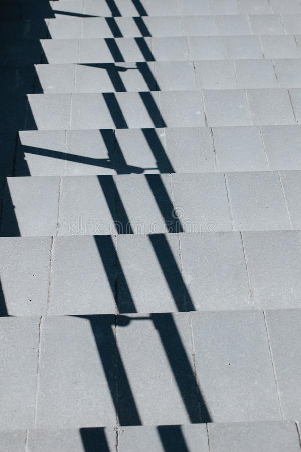 Szary schody iść w dół, z cieniem od poręcza zdjęcie royalty free