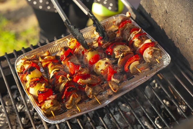 Skewers on a grill tray - rotating skewers with tongs. Szaszłyki na aluminiowej tacy ogrzewanej na grillu. Obrotowe szaszłyki ze szczypcami. Szaszł royalty free stock image