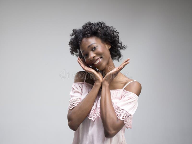 Szczęśliwa afrykańska kobiety pozycja i ono uśmiecha się przeciw szaremu tłu zdjęcie royalty free