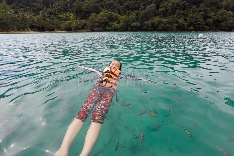 Szczęśliwa azjatykcia dziewczyny odzieży kamizelka ratunkowa, cieszy się bawić się w morza, turysty i ryby grupie w morzu, przy K fotografia royalty free