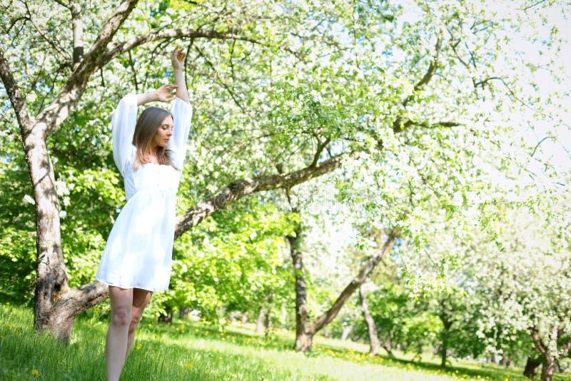 Szczęśliwa blondynki kobieta na tle kwitnący wiosna ogród z ona ręki podnosić niebo obrazy stock