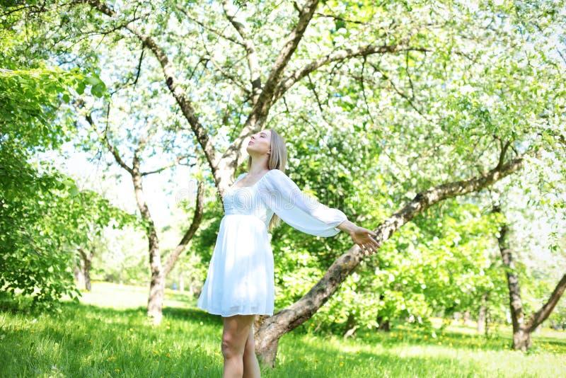 Szczęśliwa blondynki kobieta na tle kwitnący wiosna ogród z ona ręki podnosić niebo zdjęcia stock
