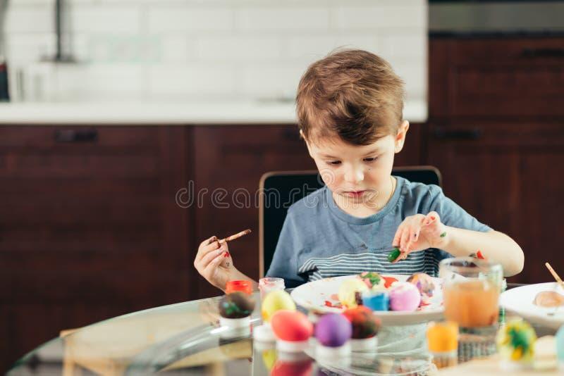 Szczęśliwa chłopiec maluje Wielkanocnych jajka, dzieci i twórczość, zdjęcia stock