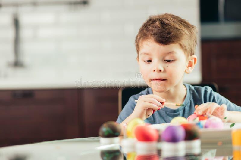 Szczęśliwa chłopiec maluje Wielkanocnych jajka, dzieci i twórczość, zdjęcia royalty free