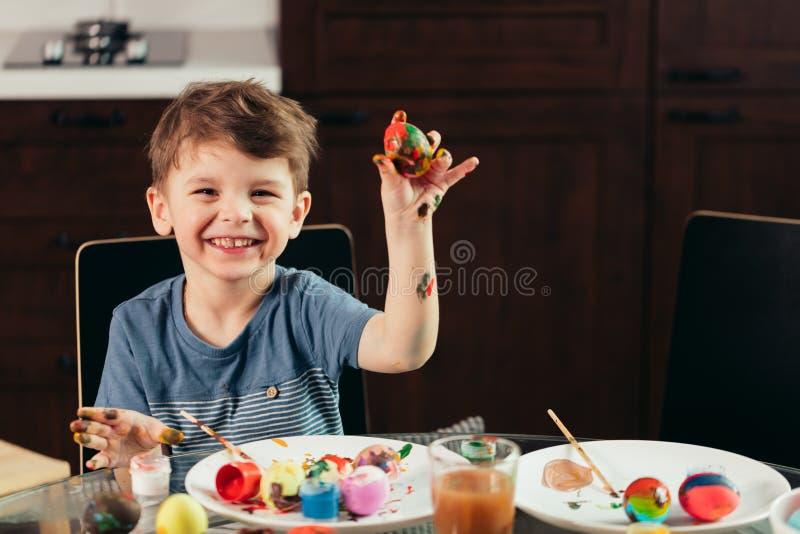 Szczęśliwa chłopiec maluje Wielkanocnych jajka, dzieci i twórczość, zdjęcie stock
