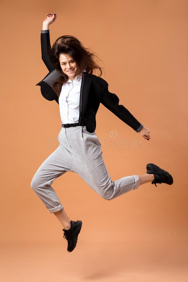 Szczęśliwa ciemnowłosa dziewczyna ubierał w białej koszula, szarych spodniach, czarnej kurtce i czarnych sneakers skokach na beżu obraz royalty free