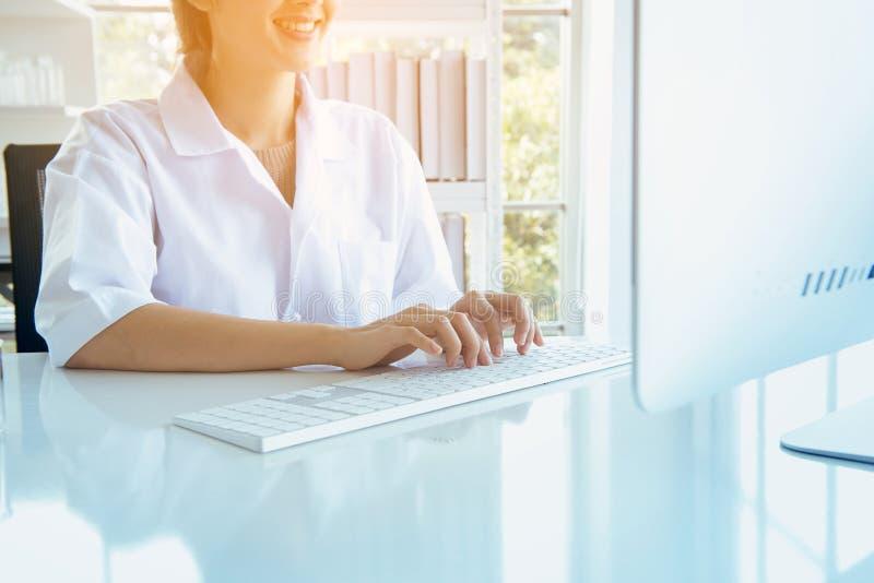 Szczęśliwa doktorska azjatykcia kobieta używa komputerową klawiaturę na biurku w biurowym pokoju, Palcowy pisać na maszynie zakoń fotografia stock