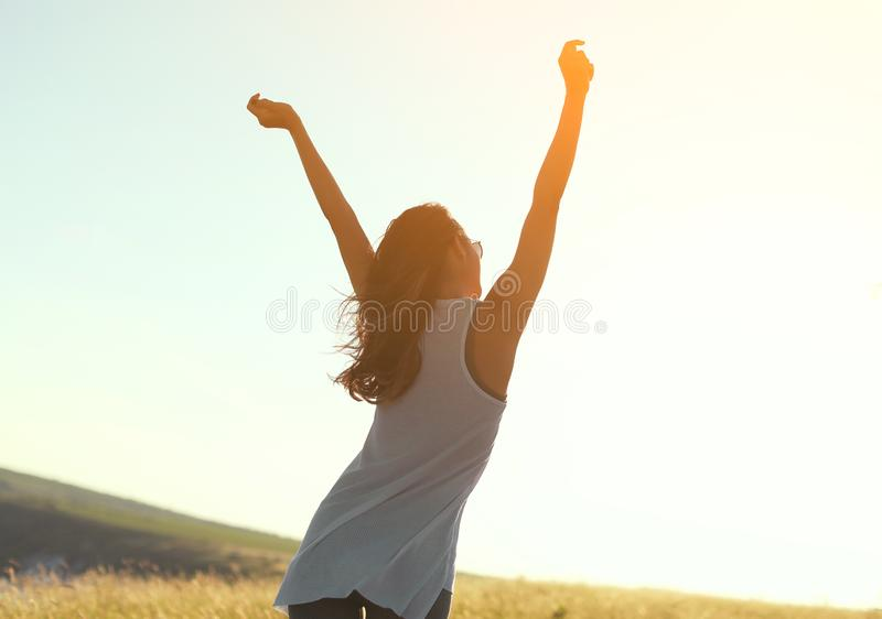 Szczęśliwa dziewczyna z rękami podnosić w świetle słonecznym zdjęcia stock