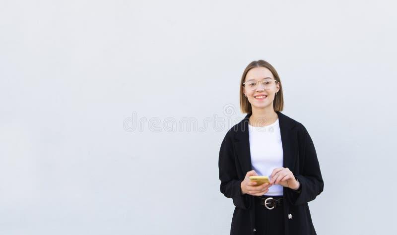 Szczęśliwa, elegancka dziewczyna w kurtce, i szkła z smartphone w jej rękach na białym tle obrazy stock
