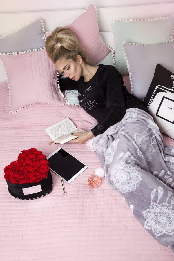Szczęśliwa kobieta lub nastoletnia dziewczyna z hełmofonami słucha muzyka od smartphone - wizerunek Piękna dziewczyna w piżamy ly fotografia royalty free