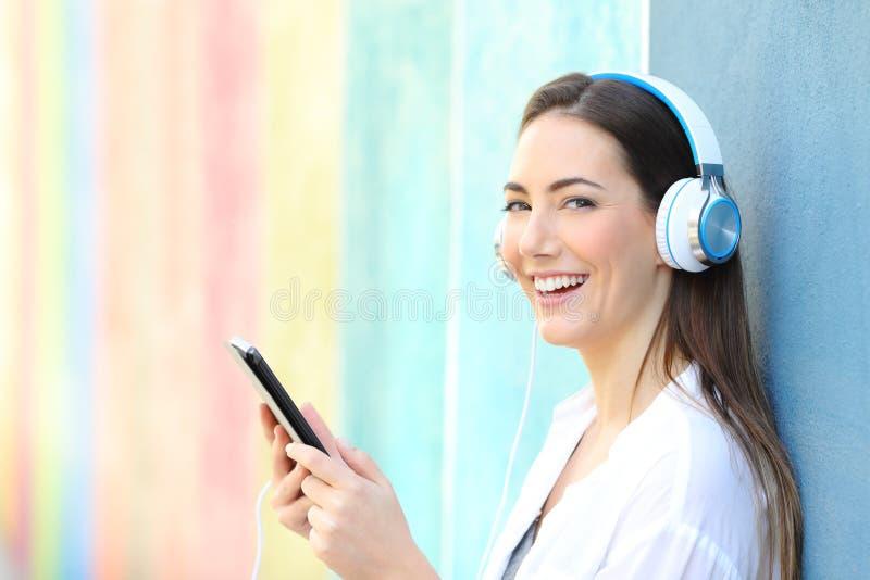 Szczęśliwa kobieta patrzeje ciebie słucha muzyka od pastylki zdjęcia royalty free