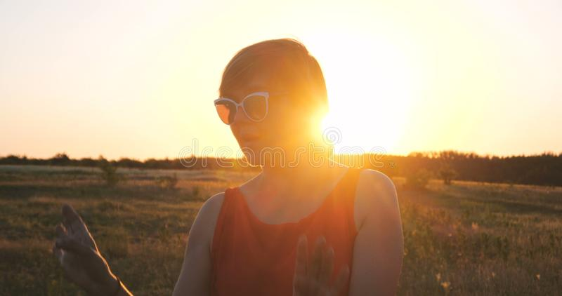 Szczęśliwa kobieta tanczy w polu przy zmierzchem w lecie w okularach przeciwsłonecznych zdjęcia royalty free