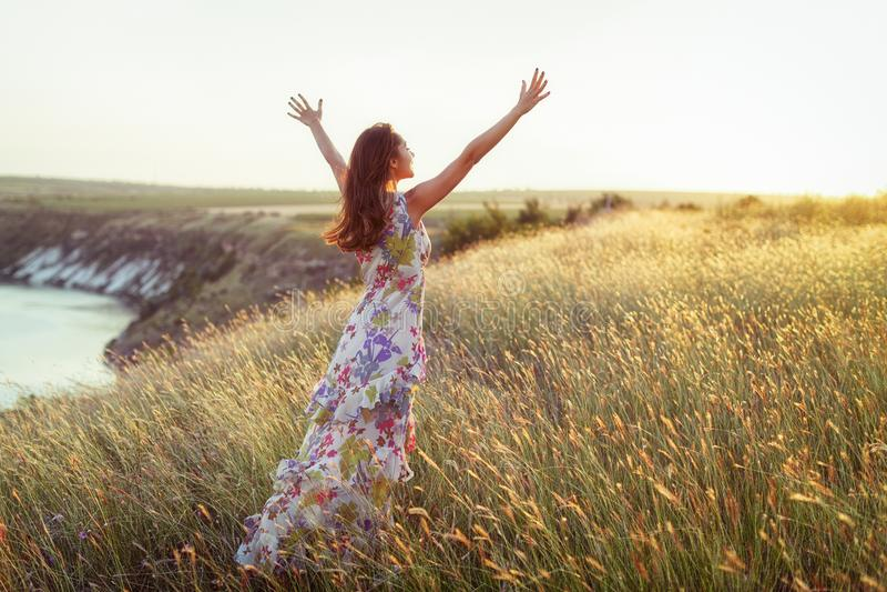 Szczęśliwa kobieta w światło sukni pozycji w trawie zdjęcie royalty free